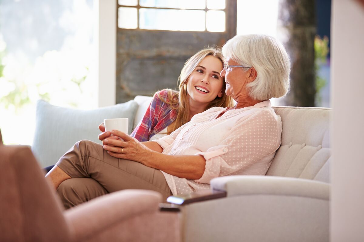 Senior woman and daughter sitting on the couch
